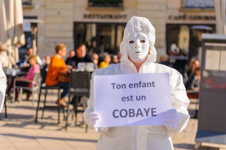 """masque blanc tenant un écriteau """"Ton enfant est un cobaye"""" à Dijon"""